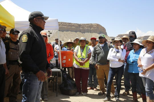 Navajo Police Capt. Dempsey Harvey, left, commends the work of volunteers in searching for Kyron Kelewood in an area north of Shiprock on June 28.