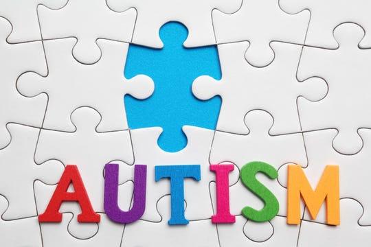 Autism inscription on a white puzzle background. Symbol of autism.