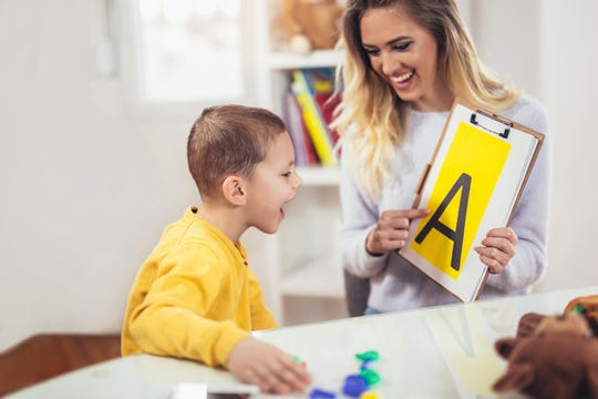 A speech therapist teaches a young autistic student the alphabet.