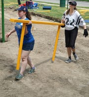 Courtney Ozog, left, and Lisa Nocerini (Wayne's City Manager) team up to move a rail section into place on June 28 at Rotary Park.