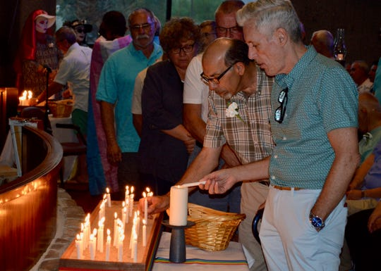 Men light candles in memory of people they knew who died of AIDS. The emotional candle lighting ceremony was held June 27, 2019, during  the United Methodist Church of Palm Springs' Stonewall Commemoration 50th Anniversary service.