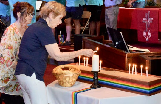 A woman lights a candle in memory of someone she knew who died of AIDS. The emotional candle lighting ceremony was held June 27, 2019, during  the United Methodist Church of Palm Springs' Stonewall Commemoration 50th Anniversary service.