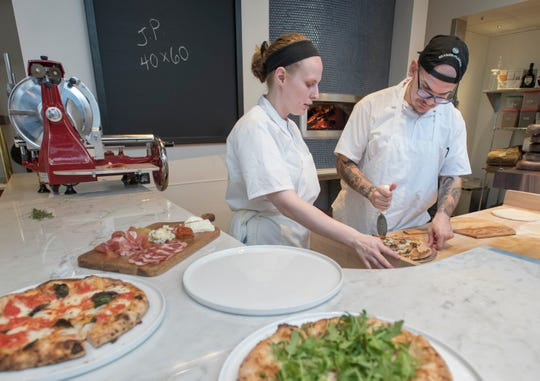 Pizza cooks Maxine Kasper and Rob Noell slice a freshly baked pizza in June at the new Angelena's Ristorante Italiano in downtown Pensacola.