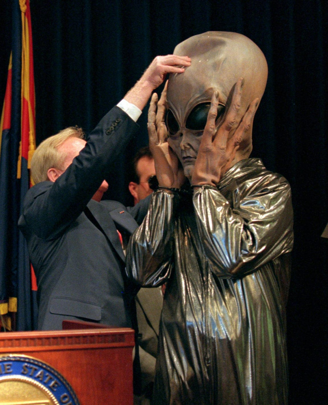 Arizona Gov. Fife Symington pulls an alien mask off  aide Jay Heiler during a news conference at the state capitol on June 19, 1997.  Symington, earlier in the day, said he would order the Arizona Department of Public Safety to look into the mysterious lights seen over Phoenix, but later insisted he was joking.