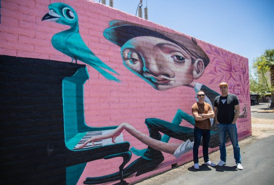 Co-founders Hartley Rodie (left) and Kell Duncan pose for a portrait outside the Churchill in downtown Phoenix on June 17, 2019. They commissioned over a dozen artists to cover their back ally with custom murals.