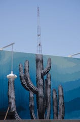A mural comissioned by co-founders of the Churchill, Hartley Rodie and Kell Duncan, is seen lined up perfectly with the broadcasting tower on top of the Westward Ho in Downtown Phoenix on June 17, 2019.