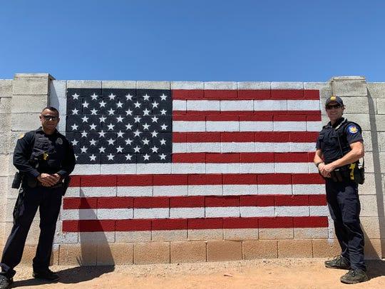 Officer Mario Lozoya and Sgt. Matt Morgan pose with the freshly repainted flag.