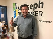 Patrick Winters, program director at St. Joseph the Worker, holds the bell people ring when they get a job. The sounds of it brings everyone out of their offices to applaud.
