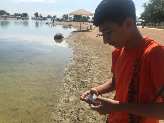 Grayson Schrader releases a small fish he caught at Surprise Community Park on June 28, 2019.