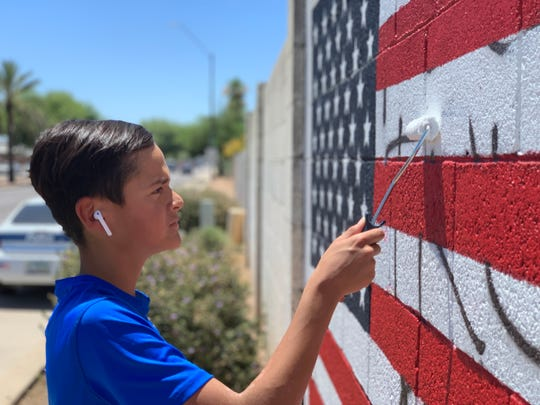 Lozoya's son paints over the anti-Trump and anti-ICE graffiti on Thursday afternoon.