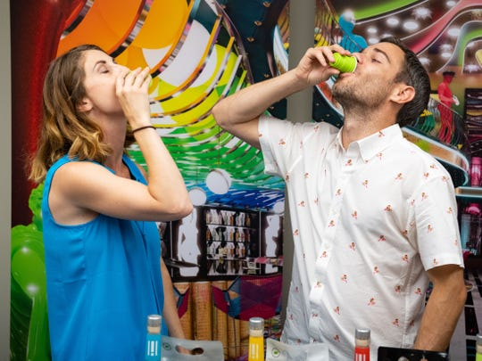Holla Spirits director of marketing and events Kat Squibb (left) and Holla Spirits co-founder Patrick Shorb take a shot, June 27, 2019.