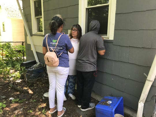 Jojo Langill and her children peek in the window of a home on Seward Street. They are looking for affordable housing, but struggle to find a a rental property that is in good condition.