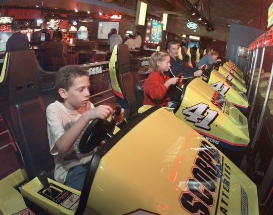 Sean Marron races against his cousin, Emily Marron on the Daytona USA 2 video games at Jillian's in downtown Rochester Wednesday, Nov. 24, 1999.
