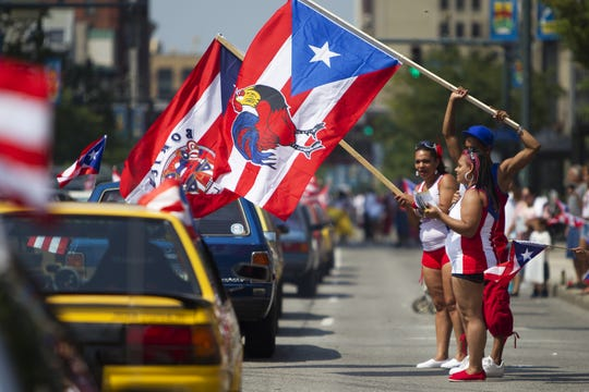 (Front to back) Jennifer Gonzalez, Mariangeli Burgos, and Bryant Burgos wave flags as the Puerto Rican Festival parade makes its way down Main Street on Saturday, August 2, 2014.