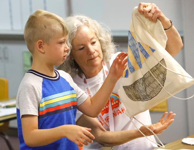Isaac Nieman works on an activity with volunteer Tara Swanson on the final day of Camp Noah at Grant School on Friday, June 28, 2019.