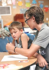 Tanner Jenkins, left, works with volunteer Nico Kramer on a questionnaire during Camp Noah at Grant School on Friday, June 28, 2019.