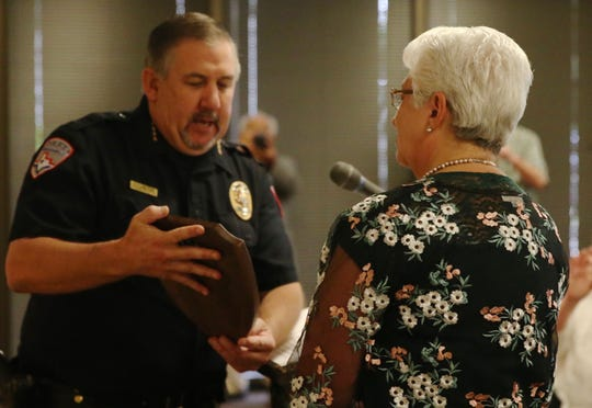 San Angelo Chief of Police Frank Carter, left, presents a plaque to retiring officer Cathy DeLaughter, right, during a ceremony at the McNease Convention Center on Friday, June 28, 2019.
