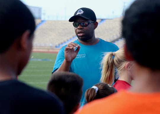 Sam Singleton coaches young athletes with the city of San Angelo Youth Track Club at San Angelo Stadium on Wednesday, June 26, 2019.