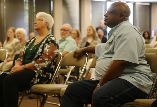 Retiring San Angelo Police Department officers Cathy DeLaughter, left, and Michael Peterson, right, listen as chief of police Frank Carter speaks during a ceremony at McNease Convention Center on Friday, June 28, 2019.