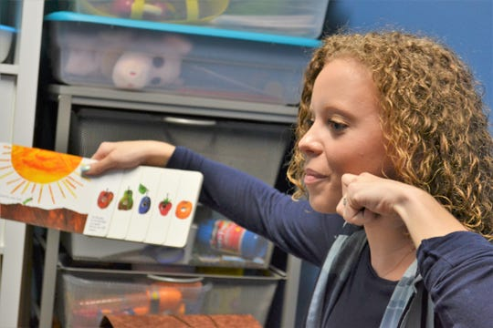 """Elizabeth Woods, a teacher at Bloom, reads """"The Very Hungry Caterpillar"""" as part of a sign language lesson Thursday, June 27, 2019. Bloom, an indoor playground and child development center in Sioux Falls, started the sign language class this month for young children as a way to help them find their voice and connect with others regardless of how they communicate."""