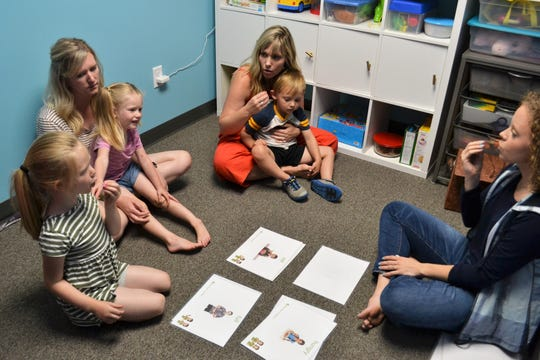 Parents Kamie Wittrock (left) and Andrea Boerigter (back) help children Ivy and Iris Wittrock and Gus Boerigter (front to back) learn sign language as teacher Elizabeth Woods (right) uses flashcards  to describe how to form certain words Thursday, June 27, 2019, at Bloom, an indoor playground and child development center in Sioux Falls. Bloom, owned by Boerigter, started the sign language class this month for young children as a way to help them find their voice and connect with others regardless of how they communicate.