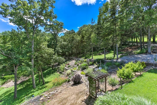 The deck of the living area looks out onto the sloping hillside and stone paths of the garden. Trees conceal the springhouse and lovely waterfall.