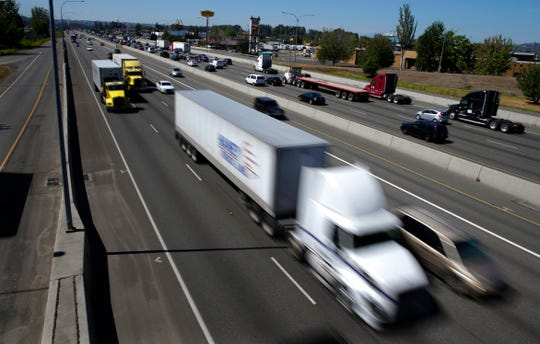 FILE - In this Wednesday, Aug. 24, 2016, file photo, truck and automobile traffic mix on Interstate 5, headed north through Fife, Wash., near the Port of Tacoma. Two U.S. senators have introduced a bill that would electronically limit tractor-trailer speeds to 65 miles per hour, a move they say would save lives on the nation's highways. Georgia Republican Johnny Isakson and Delaware Democrat Chris Coons introduced the measure Thursday, June 27, 2019.  (AP Photo/Ted S. Warren, File)