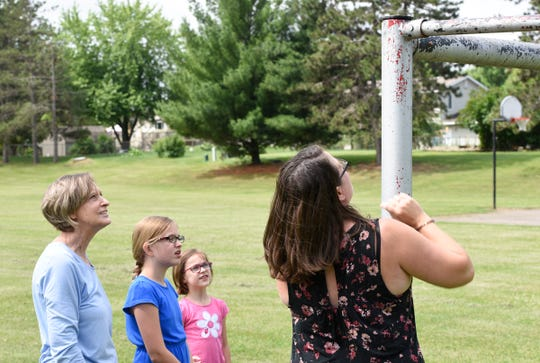 St. Joseph resident Lezlee Bergwall, right, and her children, 6-year-old Libby Bergwall and 10-year-old Adyson Bergwall, and her mother, St. Cloud resident Linda Johnson reenact finding the Granite City Days medallion on top of a soccer goal, Friday, June 28, 2019 at Southview Ninety Park.