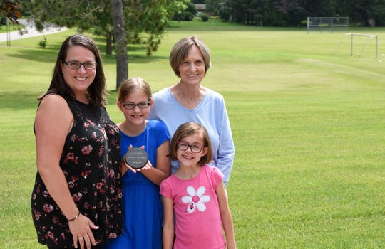 St. Joseph resident Lezlee Bergwall, left, and her children, 10-year-old Adyson Bergwall and 6-year-old Libby Bergwall, and her mother, St. Cloud resident Linda Johnson pose for a photo with the Granite City Days medallion, Friday, June 28, 2019 at Southview Ninety Park. The medallion was hidden on the top of the soccer goal in the background, which is visible from Johnson's front yard.