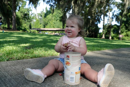 Olivia Mayo, 16 months, puts found objects from the environment into an oatmeal container to make a musical instrument from recycled household items while spending the morning with friends and her mother at Maclay Gardens Friday, June 28, 2019.