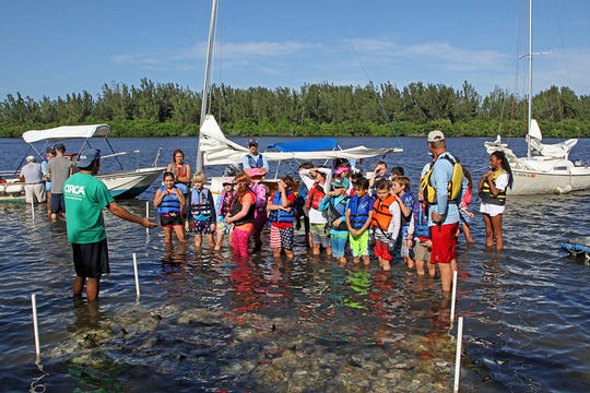 Ocean Research and Conservation Association scientist Matt Beam, left, talks to Beachland Elementary School students about the breakwater they built for the living shorelines project. Ten breakwaters have been built along the western shore of the Indian River Lagoon with the help of over 75 young sailors.