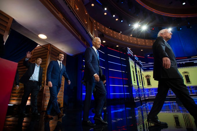 Democratic presidential primary candidates (from left) Andrew Yang, Mayor Pete Buttigieg, Vice President Joe Biden and Sen. Bernie Sanders enter the debate stage Thursday, June 27, 2019, at the Adrienne Arsht Center for the Performing Arts in Miami.