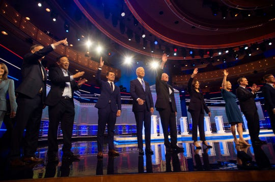 A group of Democratic presidential primary candidates (from left), Marianne Williamson, Gov. John Hickenlooper, Andrew Yang, Mayor Pete Buttigieg, Vice President Joe Biden, Sen. Bernie Sanders, Sen. Kamala Harris, Sen. Kirsten Gillibrand, Sen. Michael Bennet and Rep. Eric Swalwell, enter the debate stage Thursday, June 27, 2019, at the Adrienne Arsht Center for the Performing Arts in Miami.