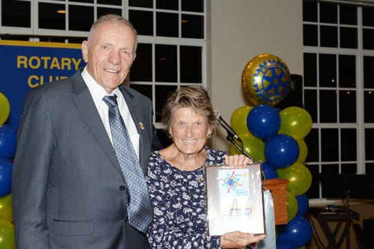 Rotarian Gary Smith, left, honors Susie Madenbach for her commitment to People Serious about Litter at the Port St. Lucie Rotary Club's 38th Annual Installation & Awards Celebration at the Santa Lucia River Club.