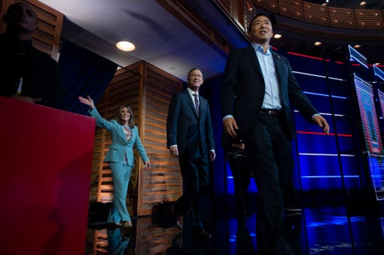 Democratic presidential primary candidates (from left) Marianne Williamson, Gov. John Hickenlooper and Andrew Yang enter the debate stage Thursday, June 27, 2019, at the Adrienne Arsht Center for the Performing Arts in Miami.