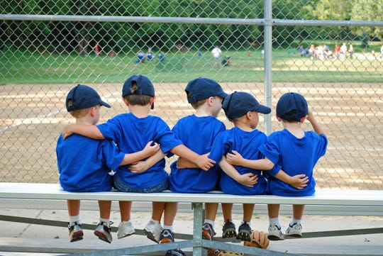 Boys put their arms around each other before their baseball game.