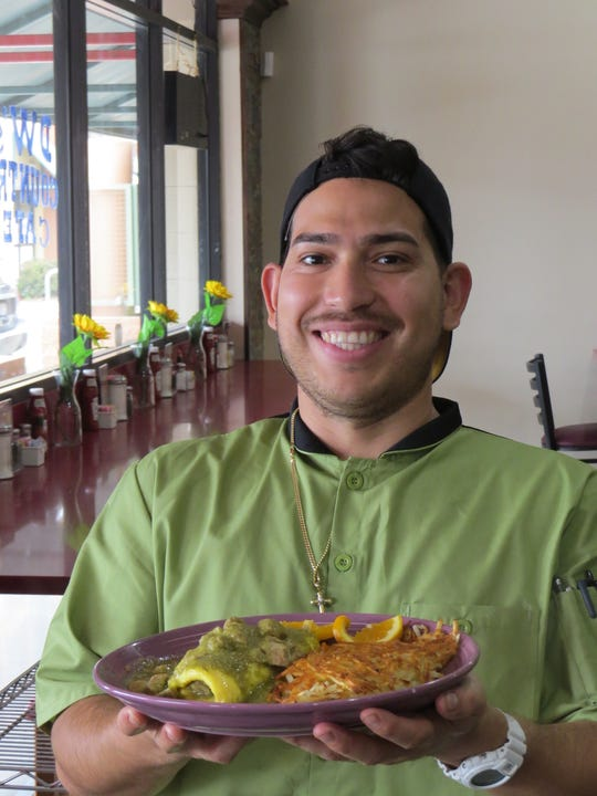Diego Garcia, chef at DW's Country Cafe in Ventura, holds an order of Mom's Chile Verde omelet with hash browns. Diners who order the dish are warned about the sauce's heat level.