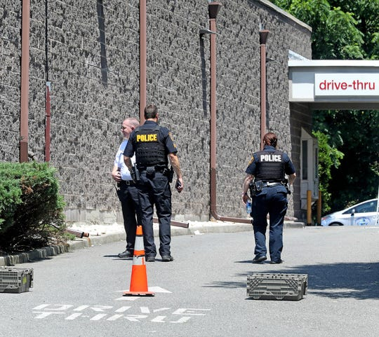 Police officers investigate the killing of a man found shot in a taxi behind the CVS Pharmacy in Ramapo, June 28, 2019.