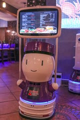 Robots guide patrons to their table at Robot Captain Crabs Cajun Seafood & Bar. Other bots help servers bring out food.