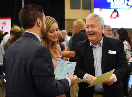 David Hartman, right, Caitlin Hartman and Treston Teague compare notes during the Wichita Falls Leadership Breakfast Friday morning at the Ray Clymer Exhibit Hall. The annual event is a fundraiser for Wichita Christian School.