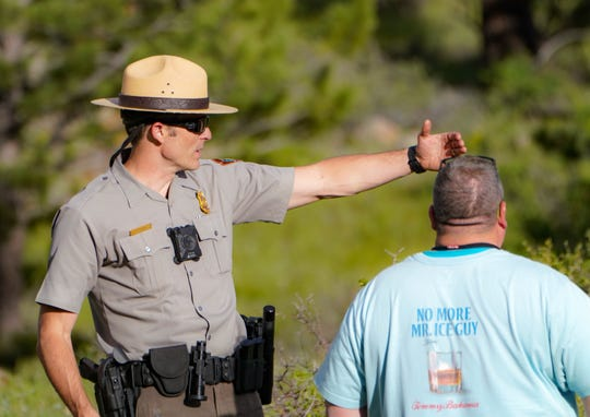 National Park Service ranger David O'Brien talks to visitor Dan Casali, after Casali and his family saw a black bear in Rocky Mountain National Park.