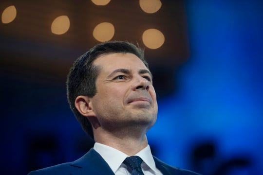 Mayor Pete Buttigieg greets the audience from the debate stage in Miami on June 27, 2019.