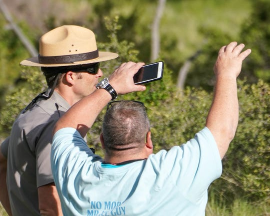National Park Service ranger David O'Brien talks to visitor Dan Casali, after Casli and his family saw a black bear in Rocky Mountain National Park.
