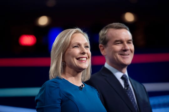 Sen. Kirsten Gillibrand, D-N.Y., and Sen. Michael Bennet, D-Colo., greet the audience from the debate stage in Miami on June 27, 2019.