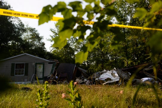 Police tape is set up outside a home where a small plane had crashed into the home late Thursday evening in Hope Mills, N.C. on Friday, June 28, 2019.   A single-engine plane crashed into the home, killing the pilot and someone inside the house, authorities said. Another person in the house was seriously hurt. (Melissa Sue Gerrits /The Fayetteville Observer via AP)