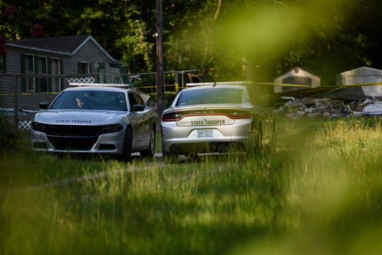 Police officers wait in their vehicles outside a home where a small plane had crashed into the home late Thursday evening in Hope Mills, N.C. on Friday, June 28, 2019.