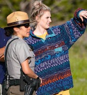 Seasonal National Park Service ranger Iliana Rosa talks with a park visitor after a black bear scampered past the road in Rocky Mountain National Park.