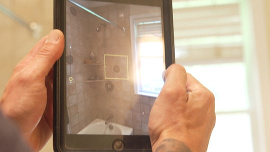 Mazza takes a photo of the bathroom shower during a routine home inspection.