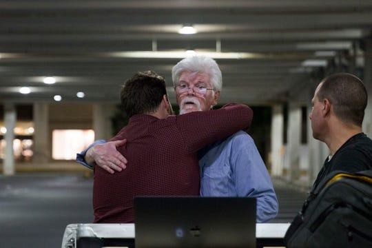 In this June 28, 2018, file photo, the Capital Gazette reporters Pat Furgurson, center, and Chase Cook hug at a makeshift office in a parking garage of a mall in Annapolis, Md., during coverage of the fatal shootings that happened in their paper's newsroom earlier in the day.