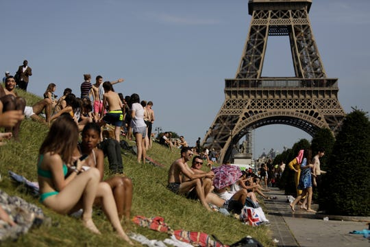 People enjoy the sun on the Trocadero gardens near the Eiffel Tower in Paris, Friday, June 28.
